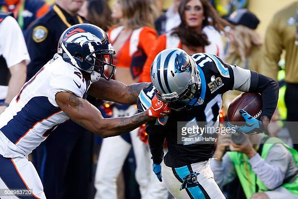 Aqib Talib of the Denver Broncos tackles Corey Brown of the Carolina Panthers by his facemask during Super Bowl 50 at Levi's Stadium on February 7...