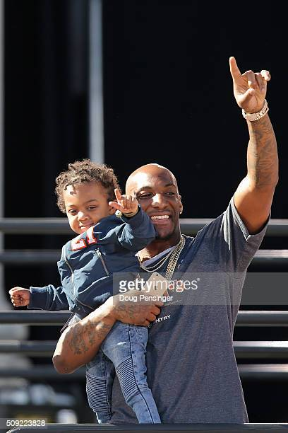 Aqib Talib of the Denver Broncos waves to the fans with one of his children as the Super Bowl 50 Champion Denver Broncos are honored at a rally on...
