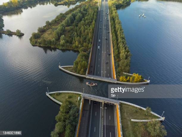 """aquaduct veluwemeer in the veluwe lake with a boat sailing in the canal - """"sjoerd van der wal"""" or """"sjo"""" stockfoto's en -beelden"""