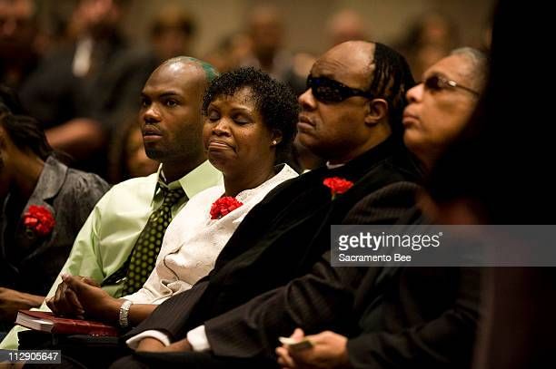 Aquanetta Gordon sits with her son Joe Johnson Jr left and Stevie Wonder right as they listen to the opening prayers at her son Ben Underwood's...