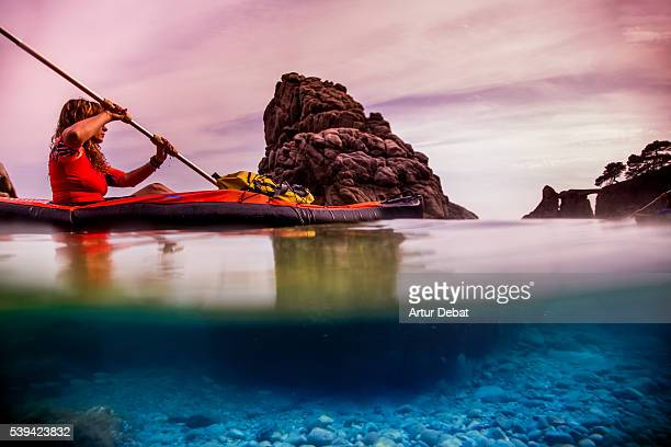 Aquatic view of an intrepid girl doing kayak in the paradise place of the Costa Brava shoreline with beautiful underwater view and action during a summertime escape.