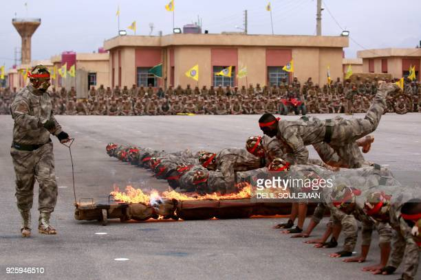 Arab and Kurdish fighters from the SelfDefense Forces take part in a graduation ceremony on March 1 in the Qamishli region / AFP PHOTO / Delil...