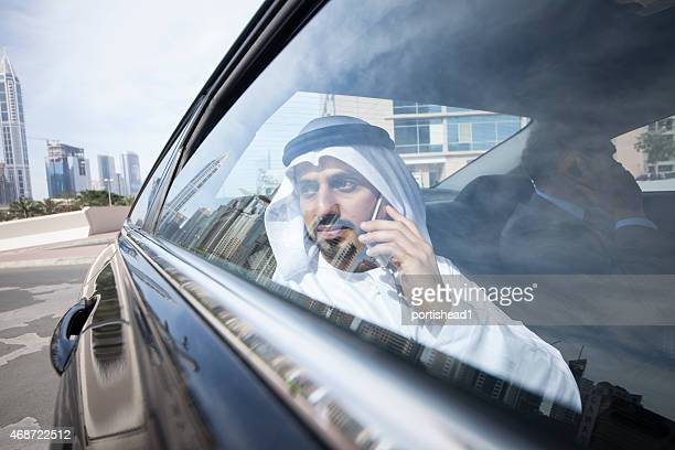 Arab and western businessmen in traditional clothes in a car