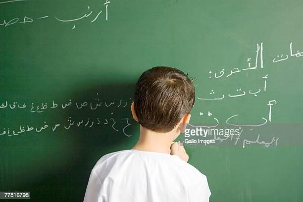 Arab Boy Writing on a Blackboard in a Classroom, Rear View. Dubai, United Arab Emirates