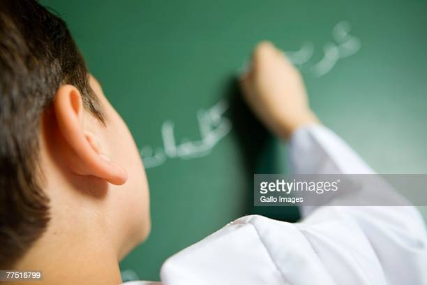 Arab Boy Writing on a Blackboard in a Classroom, Rear View. Dubai, United Arab Emirates
