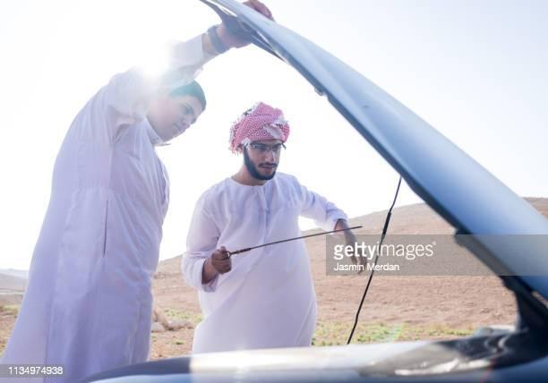 arab boys on road trip having car repair issue - car lubricants 個照片及圖片檔