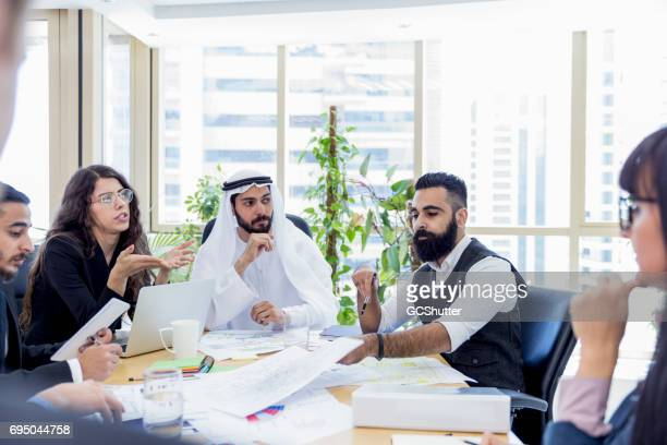 arab business executive chairing an important business meeting - middle east stock pictures, royalty-free photos & images