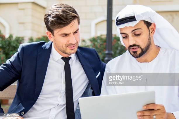 Arab business executive showing his business model using digital tablet