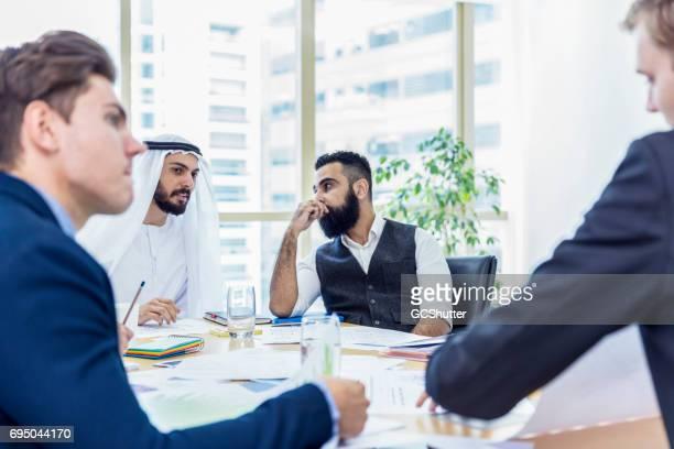 hombre de negocios árabe presidiendo una reunión de negocios, mientras hablaba con su asociado - cultura árabe fotografías e imágenes de stock