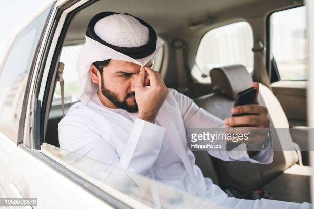 arab businessman fixing his kaffiyeh inside a taxi in the city - one mid adult man only stock pictures, royalty-free photos & images