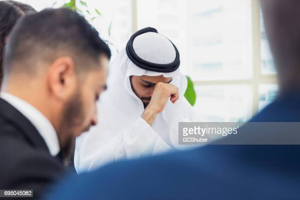 Arab businessman frustrated and tired during a corporate meeting