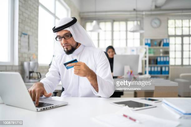 Arab businessman in modern office shopping with credit card