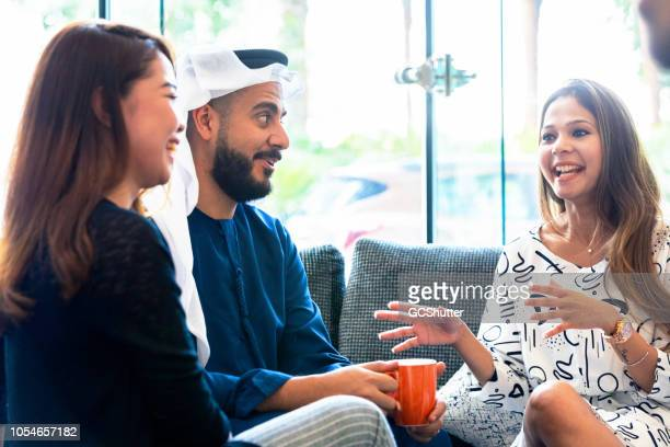 arab businessman meeting for a casual discussion with his staff - abu dhabi stock pictures, royalty-free photos & images