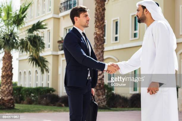 Arab businessman shaking hands with a foreign business executive