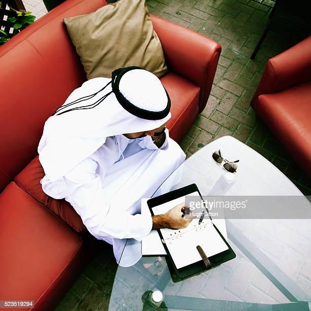 arab businessman taking notes in outdoor cafe, dubai. u.a.e - hugh sitton stock-fotos und bilder