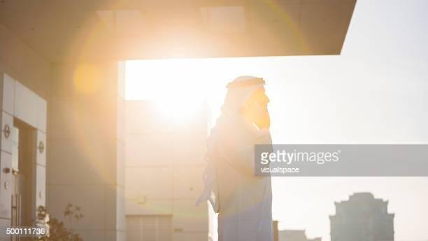 Arab Businessman Talking On Phone In Evening Sunlight