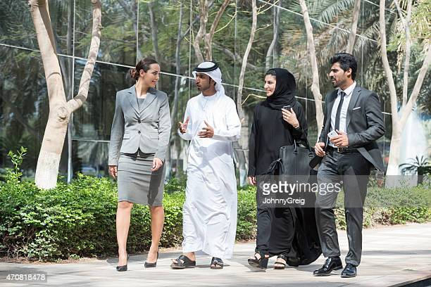 Arab businessman talking to business people outdoors