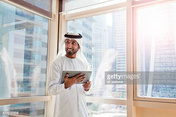 arab businessman using digital tablet in dubai office. - united arab emirates stock pictures, royalty-free photos & images
