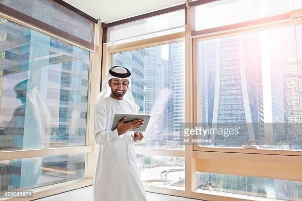 Arab businessman using digital tablet in Dubai office
