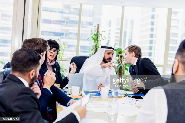 Arab businessman whispering key points during a meeting to his colleague