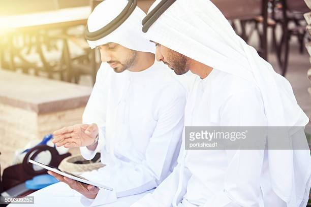 Arab  businessmen in traditional clothes and tablet