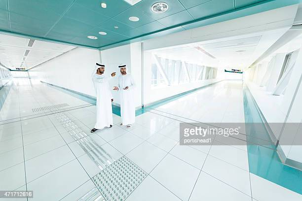 Arab  businessmen in traditional clothes in a metro