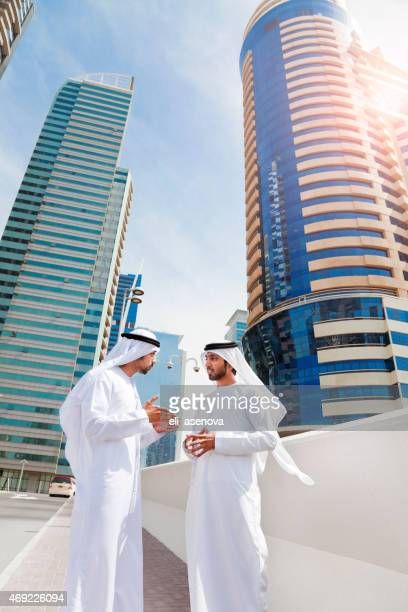 arab businessmen in traditional clothes in front of modern building. - wide angle stock pictures, royalty-free photos & images
