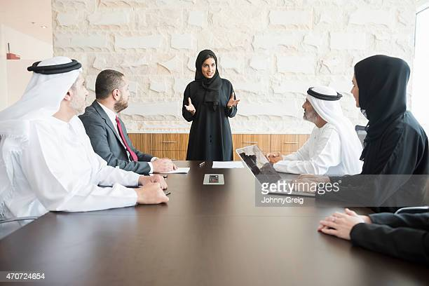 arab businesswoman giving presentation to colleagues in office - united arab emirates stock pictures, royalty-free photos & images