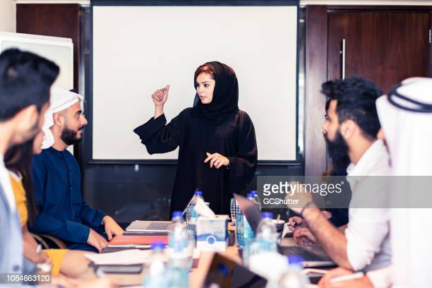 arab businesswoman leading a strategy meeting - organised group stock pictures, royalty-free photos & images