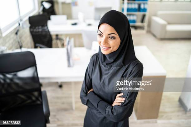 Arab businesswoman standing arms crossed in studio