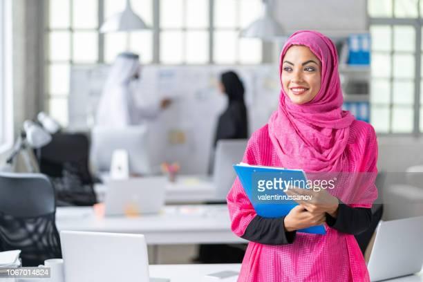 mujer de negocios árabe en trabajo moderno - equidad de genero fotografías e imágenes de stock