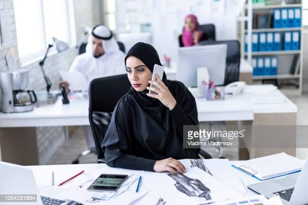Arab businesswoman talking on smart phone at work