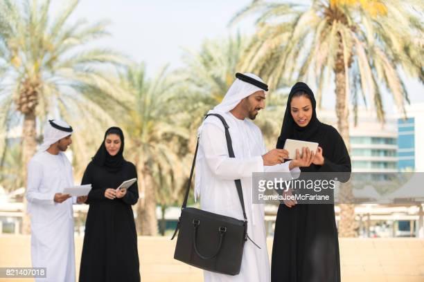arabische unternehmerinnen, unternehmer treffen außen mit handy, tablet, laptop, dokumente - persian gulf stock-fotos und bilder