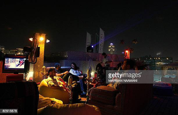 Arab clients smoke waterpipes and watch TV serials after breaking their fast at a Ramadan tent in a fivestar hotel in Dubai on September 16 2008...