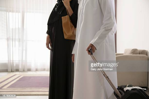 Arab couple arrive in hotel room
