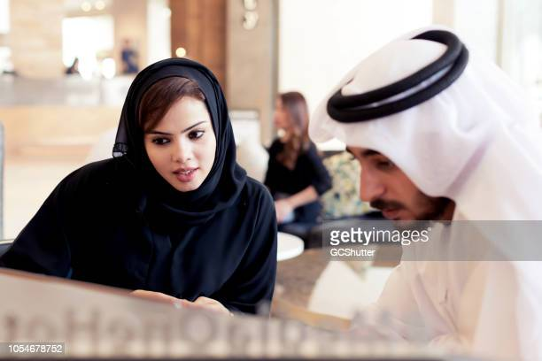 arab couple at the hotel lobby - kaffiyeh stock pictures, royalty-free photos & images