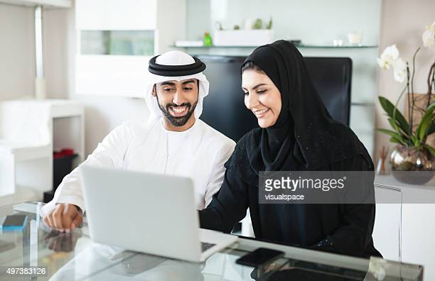 Arab Couple Discussing Business at Home Using Laptop