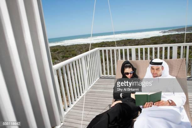 Arab couple sitting on swing reading book.