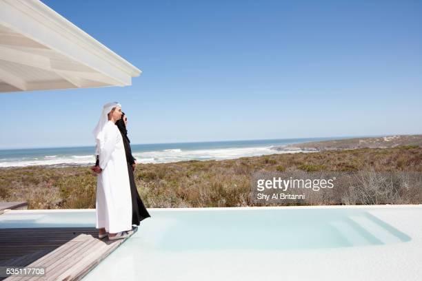 Arab couple standing on poolside.