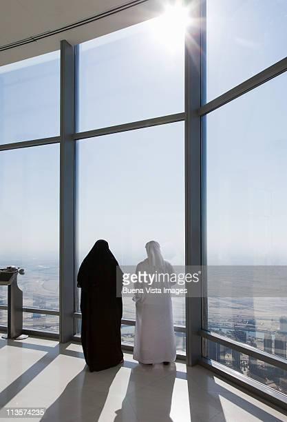 arab couple watching Dubai from Burj Khalifa