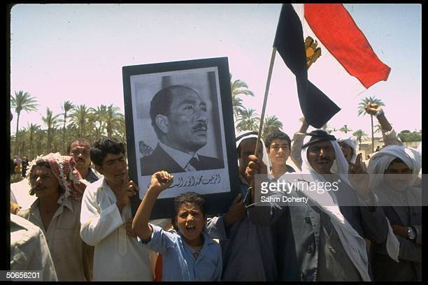 Arab crowds holding up poster emblazoned with the face of Egyptian President Anwar Sadat outside of auditorium where Israeli Prime Minister Menachem...