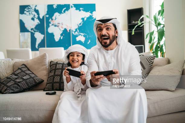 arab dad and son playing with video games at home - arabia stock pictures, royalty-free photos & images