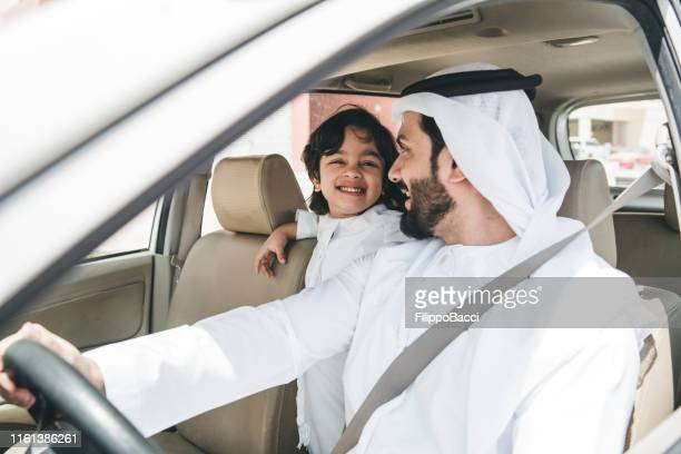 arab dad in the car with his son - car interior stock pictures, royalty-free photos & images