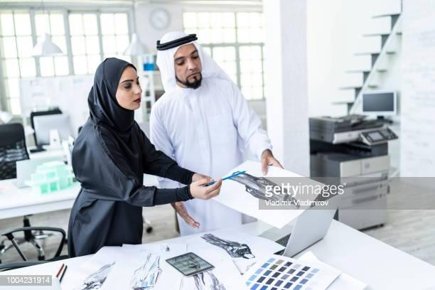 Arab designers discussing ideas at work