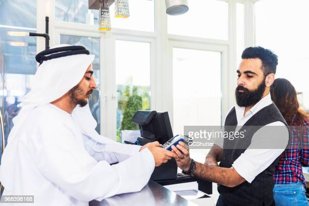 arab entering credit card pin at the checkout counter - fund fair stock photos and pictures