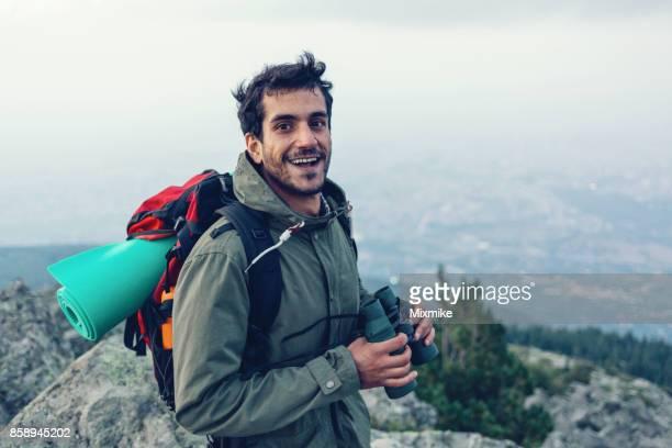 Arab ethnicity male standing on the rocky mountain peak and holding binoculars