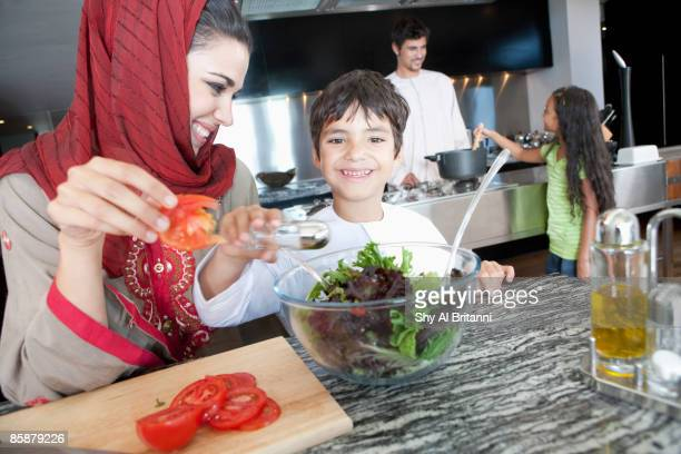 Arab family cooking in kitchen.