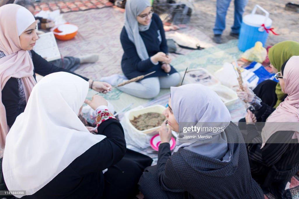 Arab family gathering around food outdoors : Stock Photo