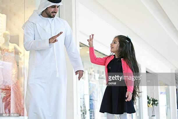 Arab family in shopping center with bags
