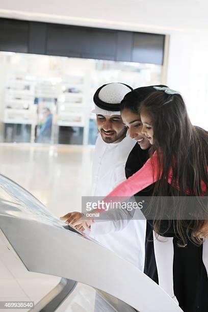 Arab family using interactive screen of digital kiosk